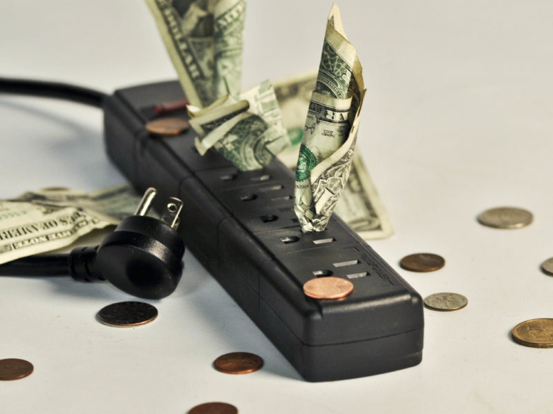 photo illustration of bills and coins scattered near a multi-outlet power extension cord