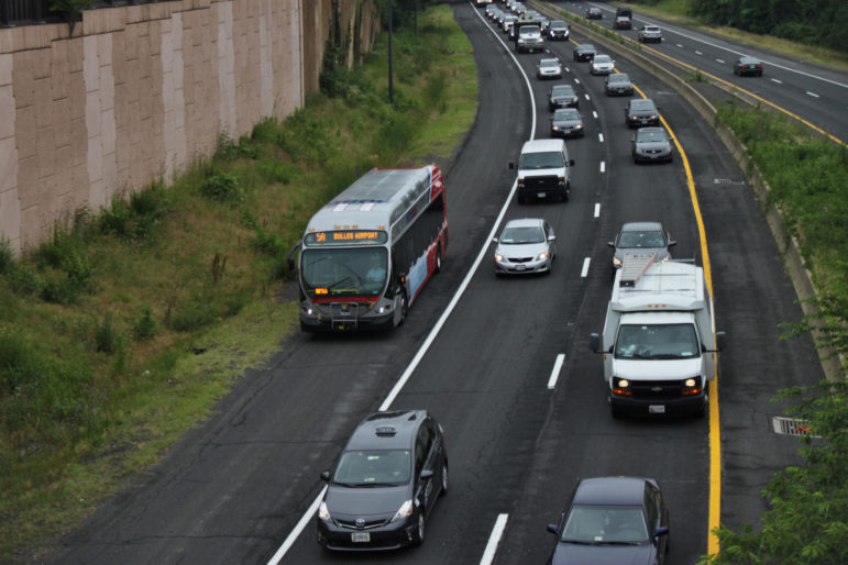 a bus travels alongside other vehicles on a highway