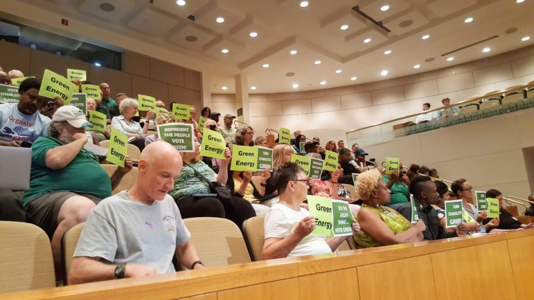 "A group of people, many holding signs with messages including ""green energy"" and ""represent the people: vote green"""