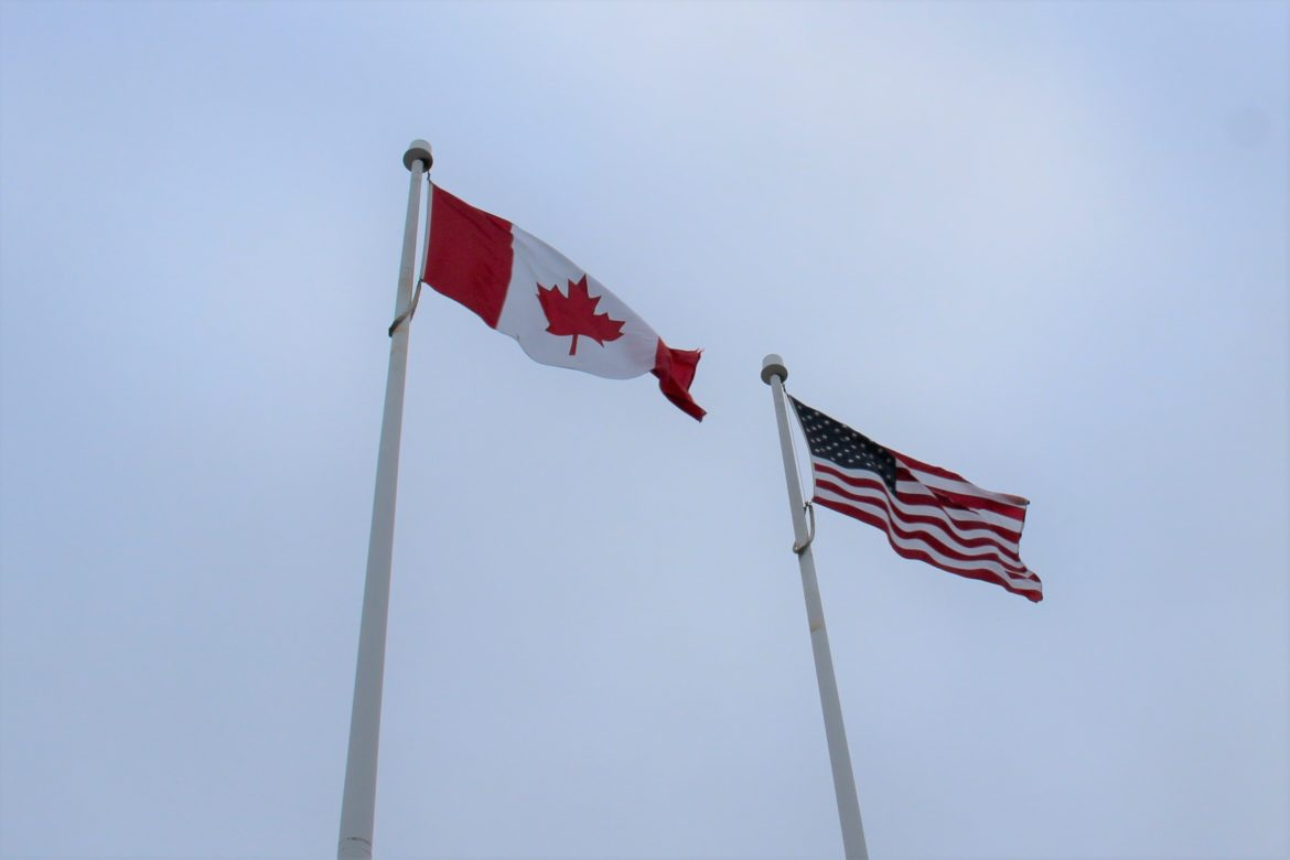 flags of the U.S. and Canada fly alongside each other