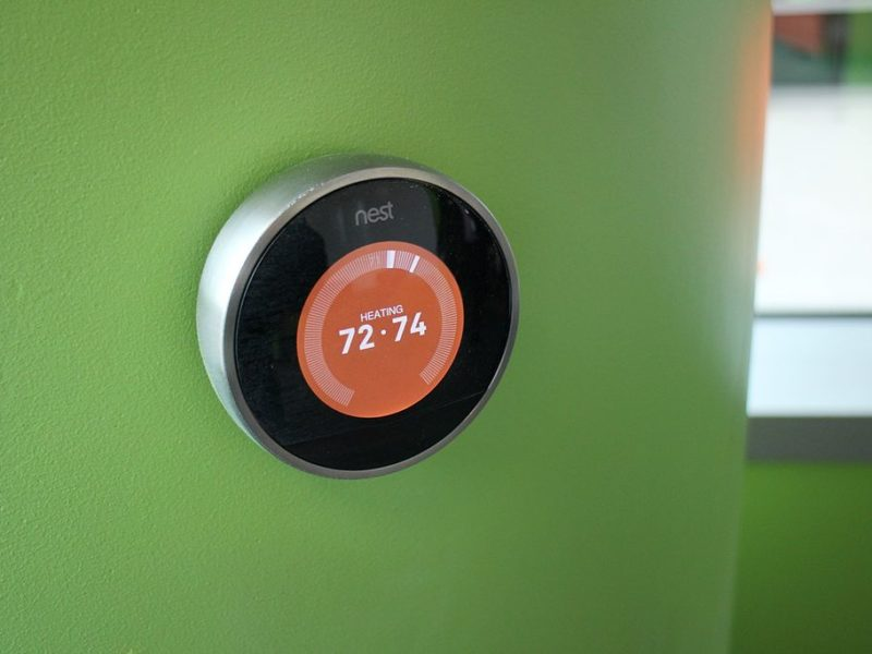 a nest thermostat on a green wall