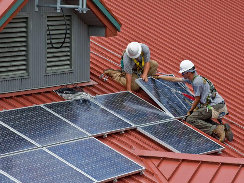 workers install solar panels on a roof