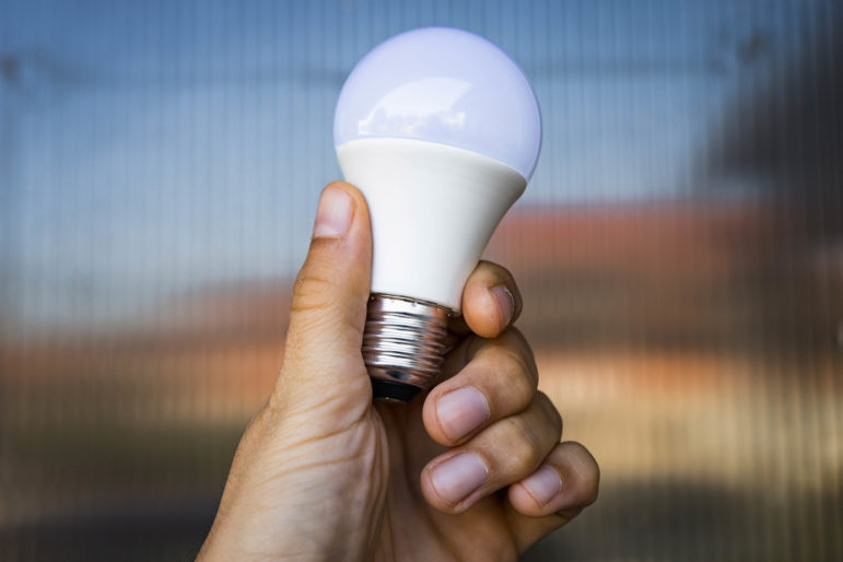 a close-up image of an LED light bulb being held in a hand