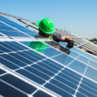 a worker in a green helmet installs a solar PV module on a rack