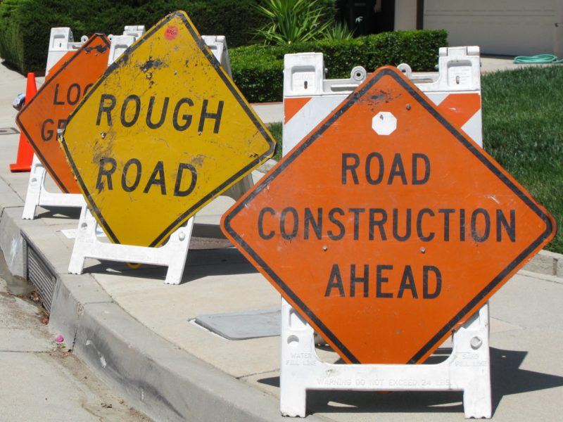 "a trio of warning signs rest on a curb, at right: ""road construction ahead""; center: ""rough road"""