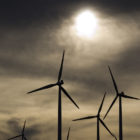 wind turbine blades are silhouetted against a cloudy sky