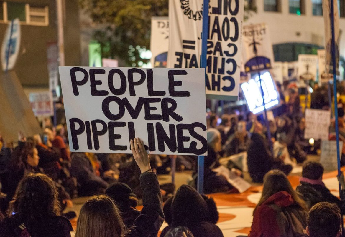 "a group of protesters: in the foreground, one holds a handwritten, black-on-white sign that reads ""PEOPLE OVER PIPELINES"""