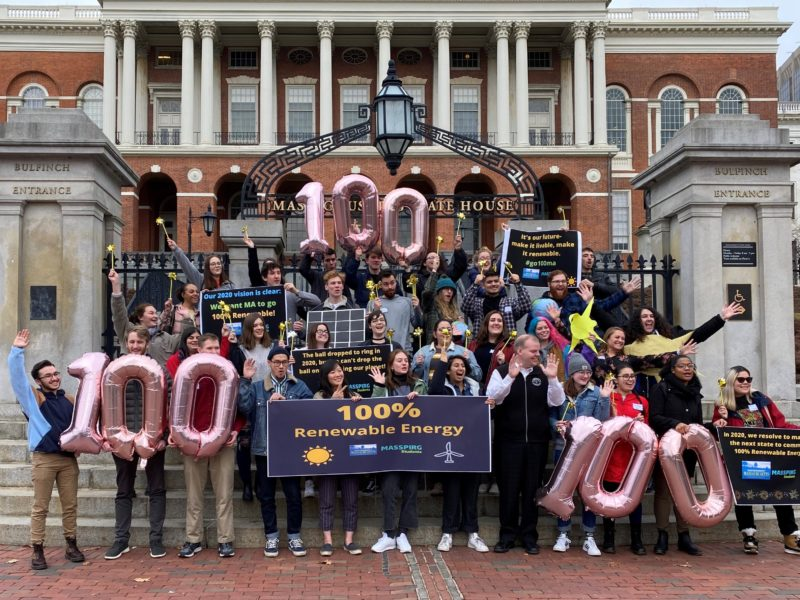 a group of several dozen people in front of the Massachusetts Statehouse, holding signs supporting 100% renewable energy