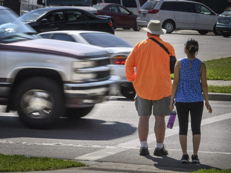 pedestrians wait to cross the street