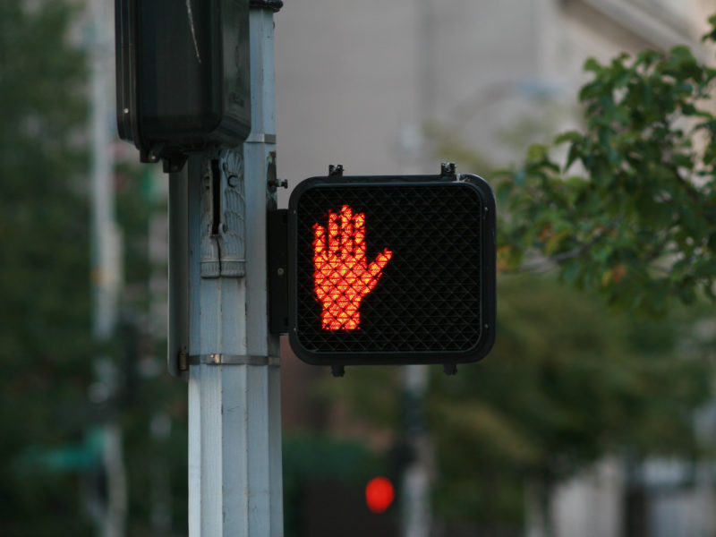 """A pedestrian crossing signal with an illuminated red hand, indicating """"don't walk."""""""