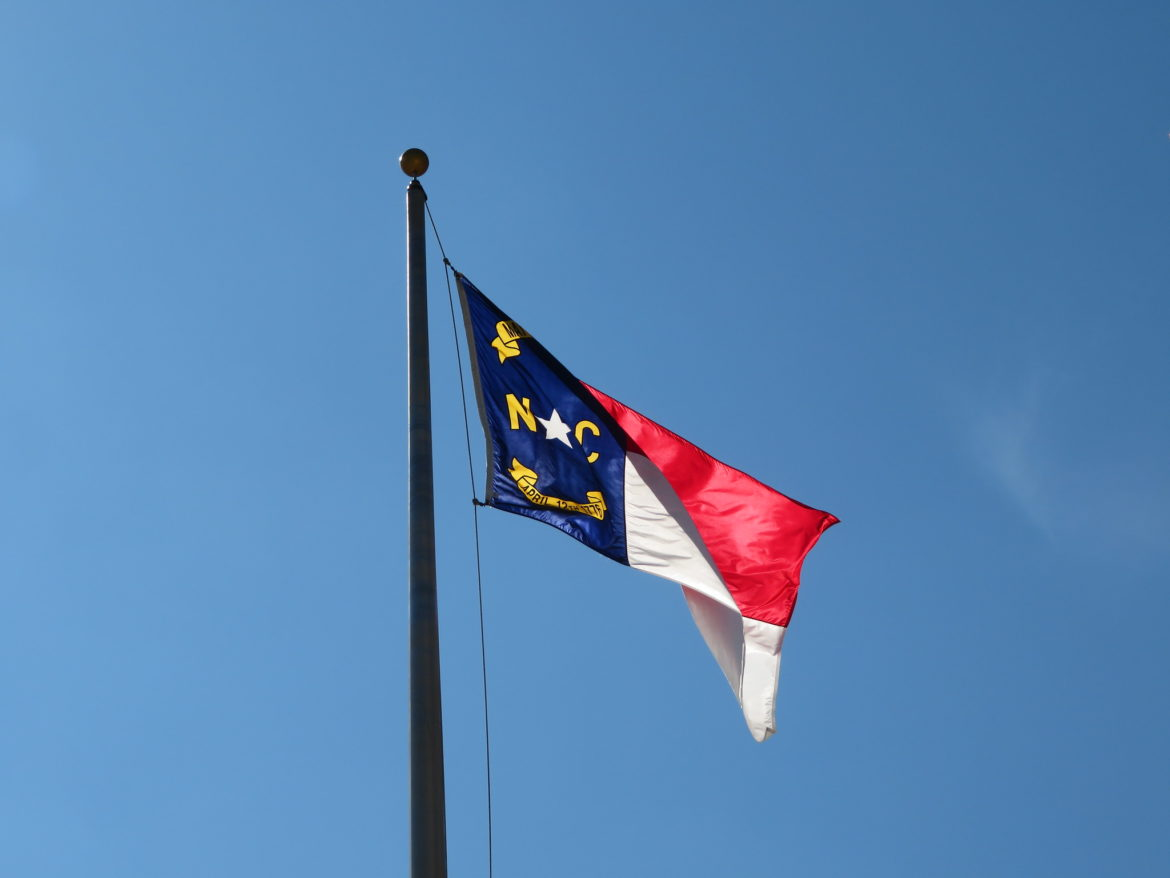 The flag of North Carolina flutters in the wind.