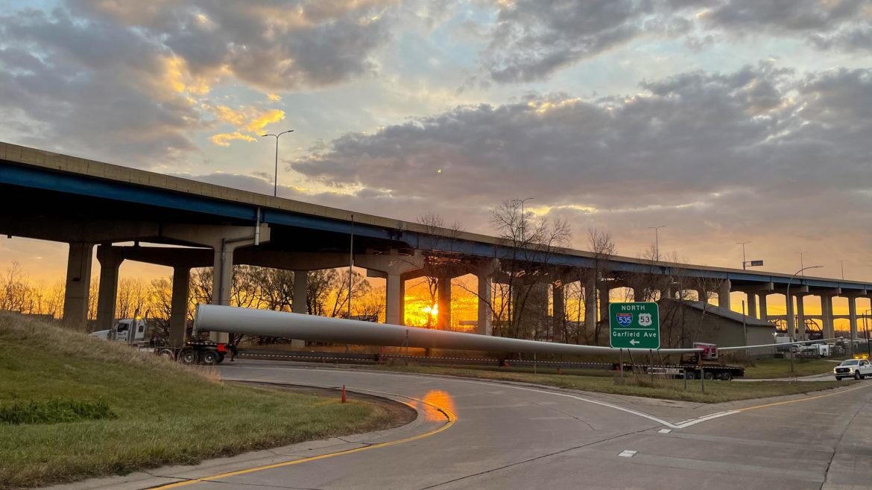 A truck hauls a wind turbine blade under an overpass.