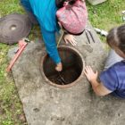 Geologist Andreana Madera-Martorell reaches into a groundwater well.