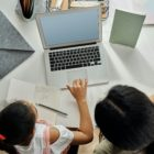 In a view from above, a parent and child sit at a desk, surrounded by books and notepads, as the child uses the trackpad on an open laptop in front of them.